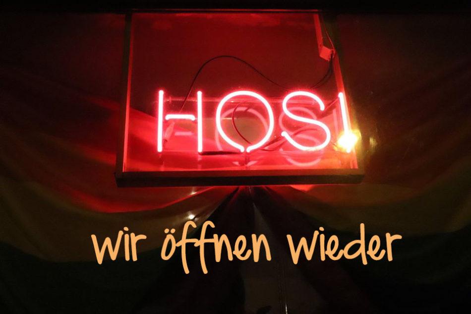 """rote Leuchtschrift """"HOSI"""" im Fenster darunter steht der Text: Wir öffnen wieder"""