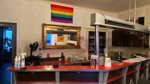 Vereinszentrum der HOSI; eine rote Bar im Vordergrund. Dahinter hängt ein großer Spiegel mit goldenem Rahmen, darüber eine Regenbogenflagge