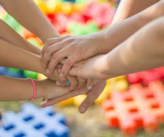 Hände von mehreren Personen, die gemeinsam zusammenhalten