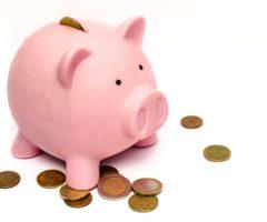 rosa Sparschwein mit Münzen, die drum rum liegen